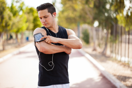 playlist: Good looking young man selecting the right song from a playlist on his smartphone before going for a run Stock Photo