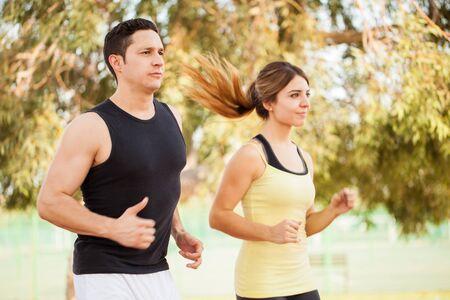 lifestyle: Attrayant jeune couple compétitif courir ensemble à l'extérieur dans un parc