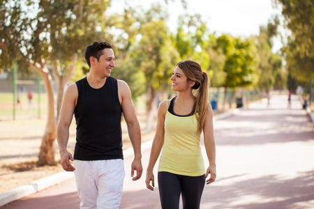 atletismo: Apuesto joven pareja flirteo y hablando mientras camina junto a una pista de atletismo al aire libre