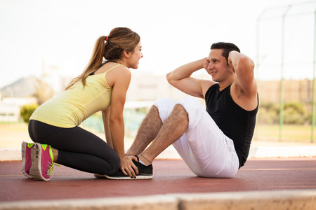 Pretty girl helping and motivating her boyfriend do some crunches outdoors Standard-Bild