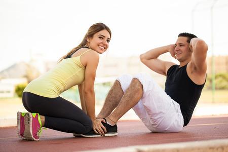 abdominal fitness: Bastante joven morena ejercicio con su novio y sosteni�ndolo hacia abajo mientras que hace unos abdominales