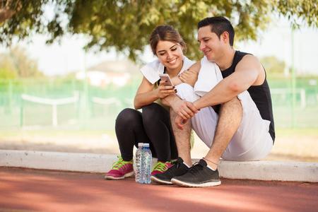 personas sentadas: Retrato de una joven pareja tomando un descanso de ejercicio juntos y mirando algunas fotos en un tel�fono inteligente