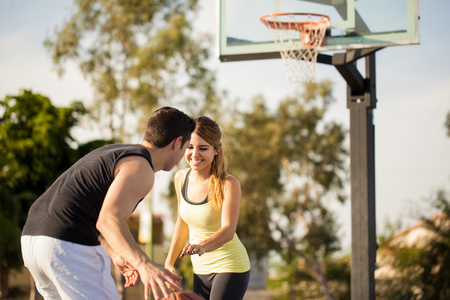 some: Pretty girl having some fun on her first date playing basketball outdoors Stock Photo