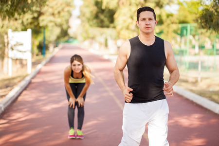 left behind: Young woman left behind by her boyfriend while running and working out together outdoors