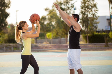 Profile view of a young man and his girlfriend playing basketball against each other on an outdoor court Banque d'images