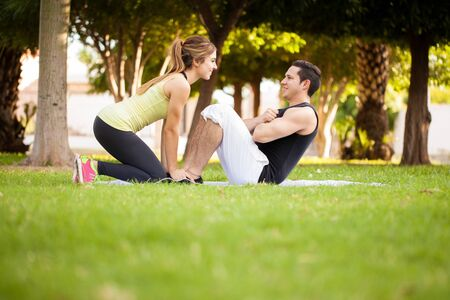 crunches: Profile view of a young couple helping each other do some crunches in a park. Lots of copy space Stock Photo