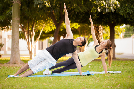 plank: Good looking young couple practicing some yoga in a park and doing a side plank together Stock Photo