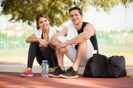 fitness hombres: Retrato de una pareja de descanso hispana linda después de trabajar juntos al aire libre y sonriente Foto de archivo