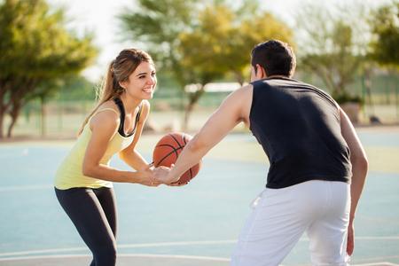 Schöne junge Frau, die Basketball spielen mit ihrem Freund auf einem Hof ??im Freien und ein bisschen Spaß