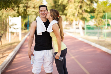 Young man in sporty outfit getting a kiss on the cheek by his girlfriend after exercising together Stock Photo