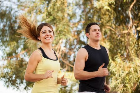 two couples: Portrait of a cute young woman jogging with her boyfriend outdoors and smiling