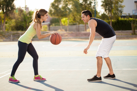 outdoor basketball court: Full length profile view of a young attractive couple playing basketball against each other outdoors Stock Photo