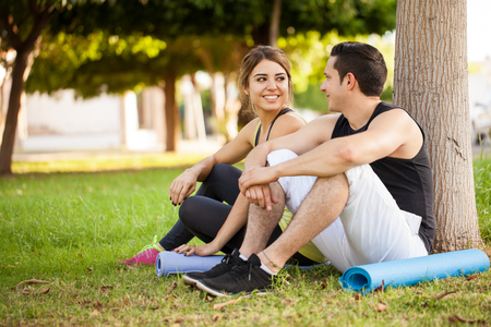 taking a break: Good looking young couple with exercise mats sitting next to a tree and flirting while taking a break from working out Stock Photo