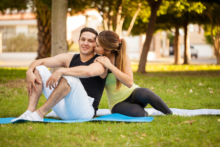 cheek: Handsome young man doing exercise with his girlfriend in a park and getting a kiss on the cheek
