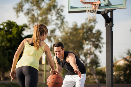 attractive couple: Attractive young couple playing basketball against each other outdoors Stock Photo