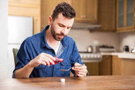 jarabe: porción del hombre joven una cucharada de jarabe para la tos para aliviar la garganta