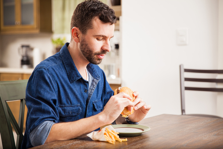 hombre comiendo: Vista de perfil de un hombre joven que goza de una hamburguesa con papas fritas en casa