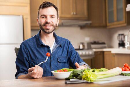 hombre comiendo: apuesto joven con una barba de comer una ensalada de un recipiente en el hogar Foto de archivo