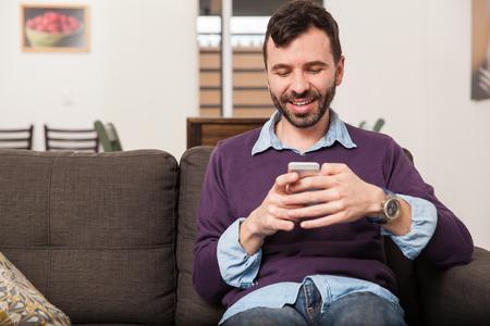 buen vivir: Hombre apuesto con una barba que usa su tel�fono inteligente y mensajes de texto mientras se est� sentado en un sof� en la sala de estar Foto de archivo