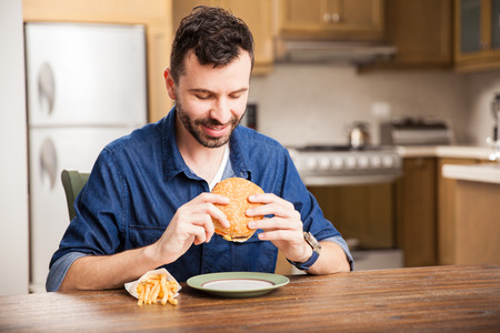 man eating: Young man with a beard and a denim shirt sitting in a dining room and eating a hamburger with fries Stock Photo