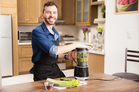 food processor: Portrait of a young Hispanic man in an apron making himself a healthy smoothie at home