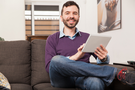 people relaxing: Portrait of a handsome young Latin man with a beard using a tablet computer at home and smiling