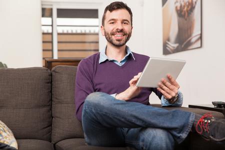 personas leyendo: Retrato de un hombre latino joven y guapo con una barba con un tablet PC en casa y sonriente