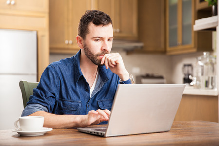 Portrait of a serious guy working on his dining room at home using a laptop