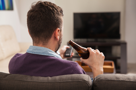 mamadera: Rear view of a young man enjoying a bottle of beer and watching some TV at home