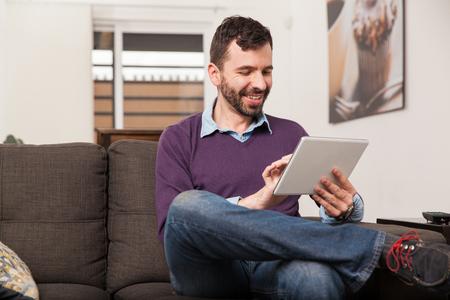 personas leyendo: Hombre joven feliz descansando en su casa y con un tablet PC en la sala de estar
