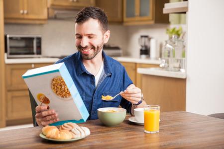 cereal: Hombre latino joven que come el desayuno en la mañana, mientras que la lectura de la caja de cereal