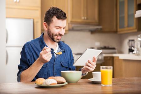 comiendo cereal: Retrato de un hombre con una barba viendo un programa de televisión en un ordenador tableta mientras disfruta de un delicioso desayuno en el país Foto de archivo