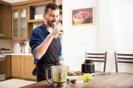 healthy men: Happy guy in an apron drinking a healthy green smoothie at home