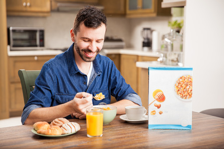 Portret van een man met een baard eten granen voor het ontbijt thuis