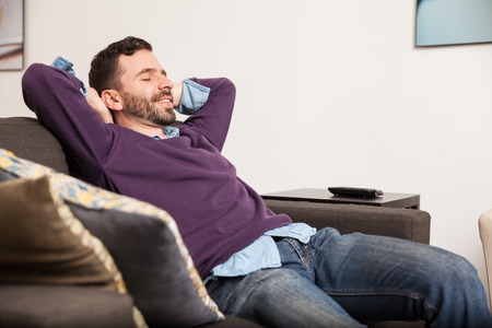 laying on back: Profile view of a handsome young man relaxing and laying back on a couch at home
