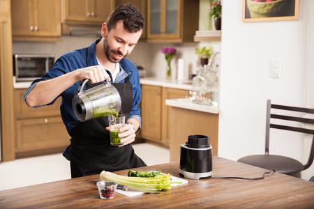 batidos de frutas: Hombre hermoso con una barba sirviéndose un poco de jugo verde para el desayuno en casa Foto de archivo
