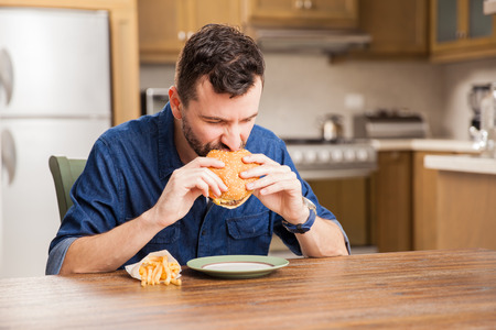 man with beard: Guy with a beard biting a hamburger while sitting in a dining room at home Stock Photo