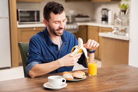 comiendo platano: joven latina con una barba pelar un plátano mientras se come el desayuno en casa Foto de archivo