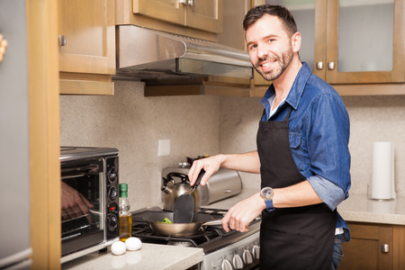 Portrait of a good looking young Hispanic man in an apron cooking something for breakfast at home Stock Photo