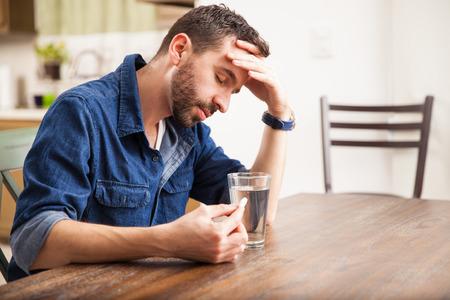 enfermos: Hombre apuesto con una barba malestar con la indigestión y el punto de beber una tableta efervescente en casa