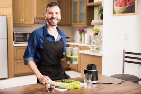 Attractive young man just prepared a green smoothie at home and smiling Zdjęcie Seryjne