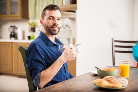 Handsome young man drinking some coffee and eating breakfast in the morning