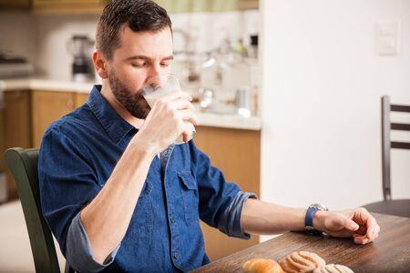 tomando leche: joven hispano con una barba beber un poco de leche de un vaso en el hogar