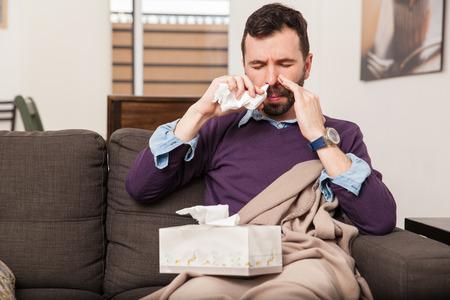 pulverizador: Retrato de un hombre joven enferma que usa el aerosol nasal para combatir la gripe en el hogar