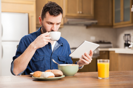 breakfast room: Latin young man with a beard eating breakfast and drinking coffee while reading the news on a tablet computer