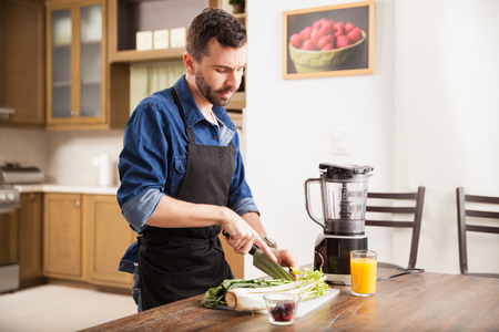 Young man chopping some celery and other greens to make a healthy smoothie at home