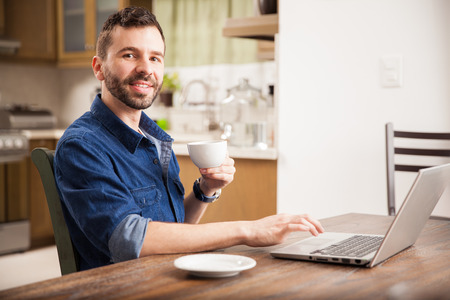 working on computer: Portrait of a young Latin man with a beard drinking some coffee and working on a laptop computer at home