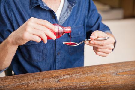 jarabe: Primer plano de un joven que sirve una cucharada de jarabe para la tos en el hogar
