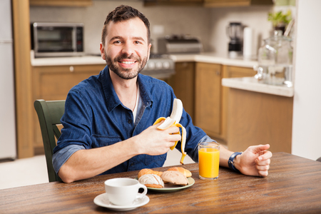 man eating: Portrait of a happy guy eating a banana and having breakfast at home Stock Photo