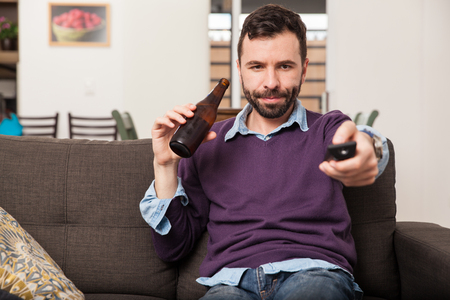hispanic people: Portrait of a Hispanic young man watching a sports game on tv and drinking beer while sitting on a couch at home Stock Photo